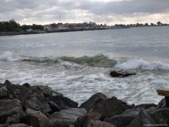 Штормовое море у пляжа за камнями